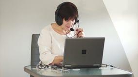 Meio moreno bonito a fêmea envelhecida dá o fones de ouvido do uso do cliente do conselho O conselheiro trabalha no serviço de as video estoque