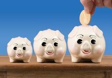 Meio pequeno e grandes mealheiros na prateleira Foto de Stock Royalty Free