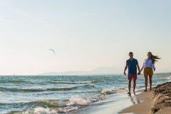 Meio rom?ntico feliz pares envelhecidos que apreciam a caminhada bonita do por do sol na praia imagem de stock royalty free