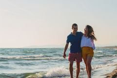 Meio rom?ntico feliz pares envelhecidos que apreciam a caminhada bonita do por do sol na praia foto de stock