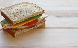 Meio sanduíche do presunto e do queijo na placa de estaca de madeira Fotografia de Stock Royalty Free