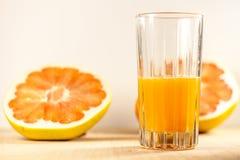 Meio vidro do suco de laranja recentemente espremido imagens de stock royalty free