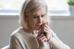 Meio virado mulher envelhecida que limpa o lo deprimido de sentimento de grito dos rasgos foto de stock