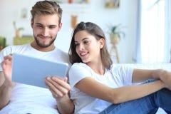 Meios de observação dos pares novos satisfeitos em linha em uma tabuleta que senta-se em um sofá na sala de visitas imagens de stock
