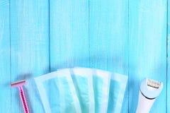 Meios para a remoção do cabelo Epilator, lâmina para barbear, tiras da cera em uma folha tropical em um fundo de madeira azul Epi fotos de stock royalty free