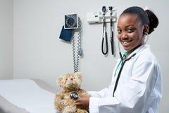 Meisje arts die stethoscoop op teddybeer met behulp van Royalty-vrije Stock Afbeeldingen
