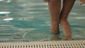 Meisje in badpak die aan de rand van de pool komen en in zwembad gaan stock footage
