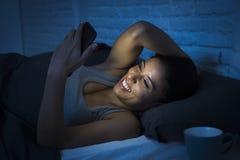 Meisje in bed die mobiele telefoon met behulp van laat bij nacht die bij donkere slaapkamer gelukkig en ontspannen liggen Royalty-vrije Stock Afbeeldingen