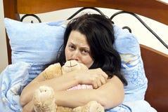 Meisje in bed met een stuk speelgoed royalty-vrije stock afbeelding
