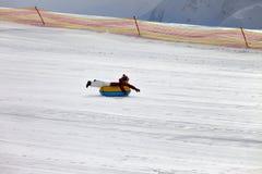 Meisje bergaf op sneeuwbuis bij de skitoevlucht Royalty-vrije Stock Fotografie