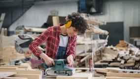 Meisje in beschermende hoofdtelefoons die hout met riemschuurmachine bezig oppoetsen in workshop stock videobeelden