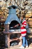 Meisje bij de barbecue Stock Afbeeldingen