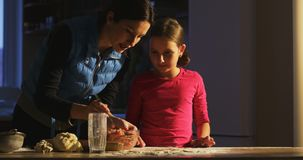 Meisje bij de lijst klaar om met moeder te koken die weinig chef-kok leren stock video