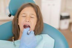 Meisje bij de ontvangst in dentist& x27; s bureau Meisjezitting als voorzitter dichtbij een tandarts na tandbehandeling stock afbeelding