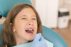 Meisje bij de ontvangst in dentist& x27; s bureau Meisjezitting als voorzitter dichtbij een tandarts na tandbehandeling stock foto
