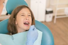 Meisje bij de ontvangst in het bureau van de tandarts Meisjezitting als voorzitter dichtbij een tandarts na tandbehandeling littl stock fotografie