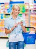 Meisje bij de winkel met schoonheidsmiddelen in handen Stock Afbeelding