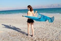 Meisje bij dood overzees strand Stock Foto's