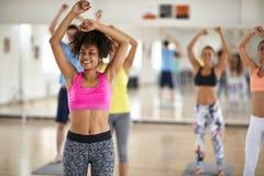 Meisje bij groep de cardio opleiding in geschiktheidscentrum stock foto's
