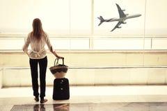 Meisje bij het luchthavenvenster die aan kijken stock foto