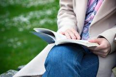 Meisje bij het park dat een boek leest stock afbeeldingen