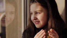 Meisje bij het venster met een kop van koffie stock video