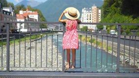 Meisje bij hoed op de dijk van een bergrivier in een Europese stad stock videobeelden
