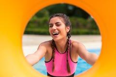 Meisje bij pool die een goede tijd hebben, die met rubbervlotter spelen stock foto