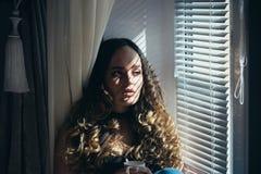 Meisje bij venster met kop thee of koffie stock foto