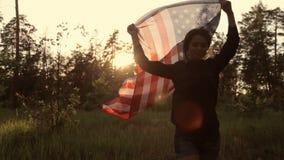 Meisje bij zonsondergang met Amerikaanse vlag in handen stock videobeelden
