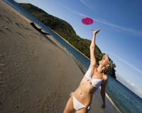 Meisje in bikini die een frisbee vangt Stock Afbeelding