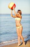 Meisje in bikini het spelen bal op het strand Stock Foto's
