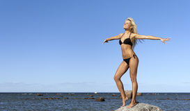 Meisje in bikini het stellen op een rots dichtbij het overzees Royalty-vrije Stock Foto's