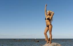 Meisje in bikini het stellen op een rots dichtbij het overzees Royalty-vrije Stock Foto
