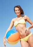 Meisje in bikini met bal op het strand Royalty-vrije Stock Afbeeldingen