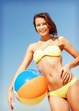 Meisje in bikini met bal op het strand Stock Foto