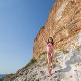 Meisje in bikini onder kustrotsen stock foto's