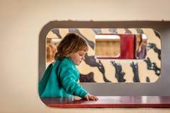 Meisje binnen een stuk speelgoed huis Stock Afbeelding