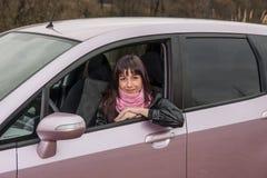 Meisje binnen roze auto Stock Afbeelding