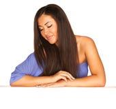 Meisje in blauwe kleding achter witte raad stock foto