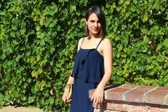 Meisje in blauwe kleding dichtbij een muur van bladeren Royalty-vrije Stock Foto's