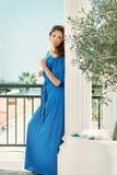 Meisje in blauwe kleding die zich door Griekse kolommen en olijfboom bevinden Royalty-vrije Stock Fotografie