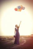Meisje in blauwe kleding met boeket en ballons Royalty-vrije Stock Afbeeldingen