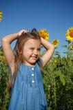 Meisje in blauwe kleding op een gebied van zonnebloemen Royalty-vrije Stock Afbeelding