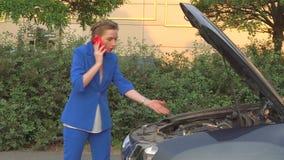 Meisje in blauwe kostuumtribunes voor gebroken auto en besprekingen op telefoon Zij is emotioneel De vrouw roept over hulp zij stock videobeelden