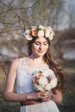 Meisje, bloemenkroon en de lentebos Royalty-vrije Stock Afbeeldingen