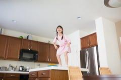 Meisje bovenop keuken tegenbovenkant stock afbeeldingen