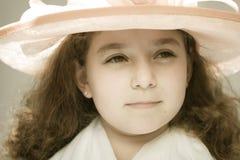 Meisje in buitensporige hoed stock afbeelding