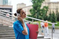Meisje dat aan muziek op hoofdtelefoons luistert Stock Foto