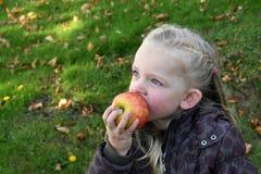 Meisje dat appel eet Stock Afbeelding